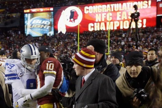 Washington quarterback Robert Griffin III offers some kind words to Dallas' Tony Romo after the Redskins knocked the Cowboys out of the playoff picture. (Rob Carr / Getty Images / December 29, 2012)